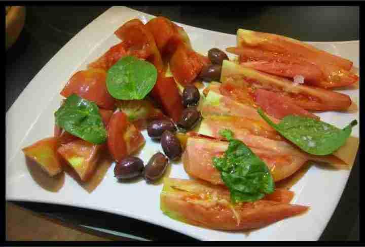 Ensalada de tomates variados con aceitunas de kalamata y albahaca, aov y sal Maldon.