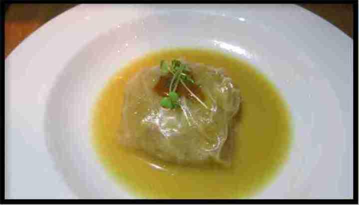 Raviolini de pasta de arroz relleno de chucrut y regado con caldo miso.